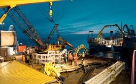An der 10 m Tiefenlinie wird vom Kabelschiff die Länge an Seekabel auf eine Barge umgespult, die erforderlich ist, um von dieser Stelle aus die erste Anschlussstelle am Festland zu erreichen. Dieser Vorgang ist erforderlich, weil nur eine Barge bis auf den Strand manövrieren kann, um sich dort trocken fallen zu lassen.